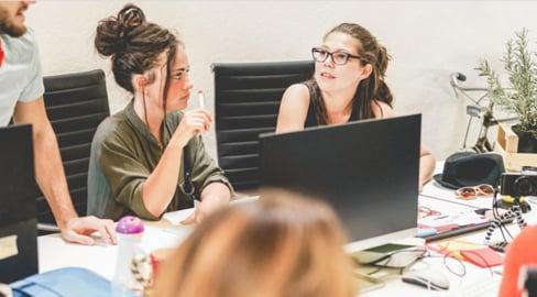 Naisia työskentelemässä pöydän ympärillä