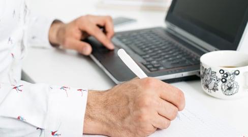 tietokone ja miehen kädet