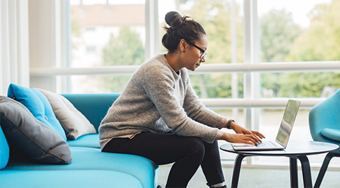 A woman at the computer sitting an a blue sofa