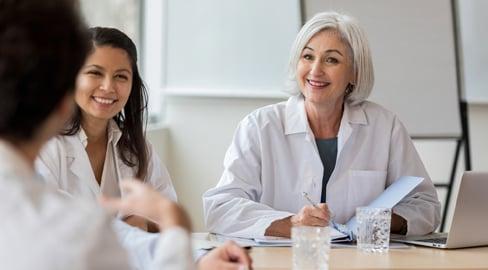 Hoitohenkilökuntaa keskustelemassa pöydän ääressä
