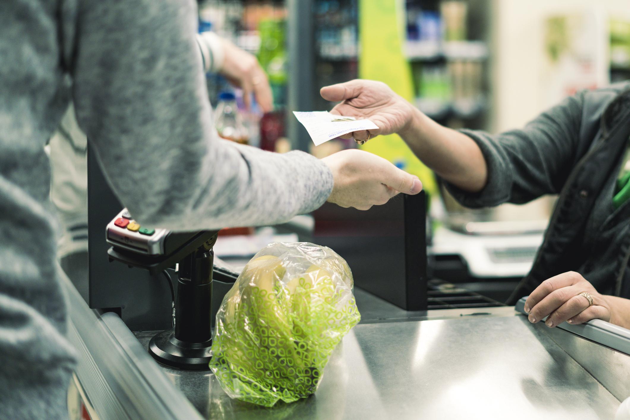 Ruokakaupan kassatyöntekijä antaa kuitin ja vaihtorahat asiakkaalle.