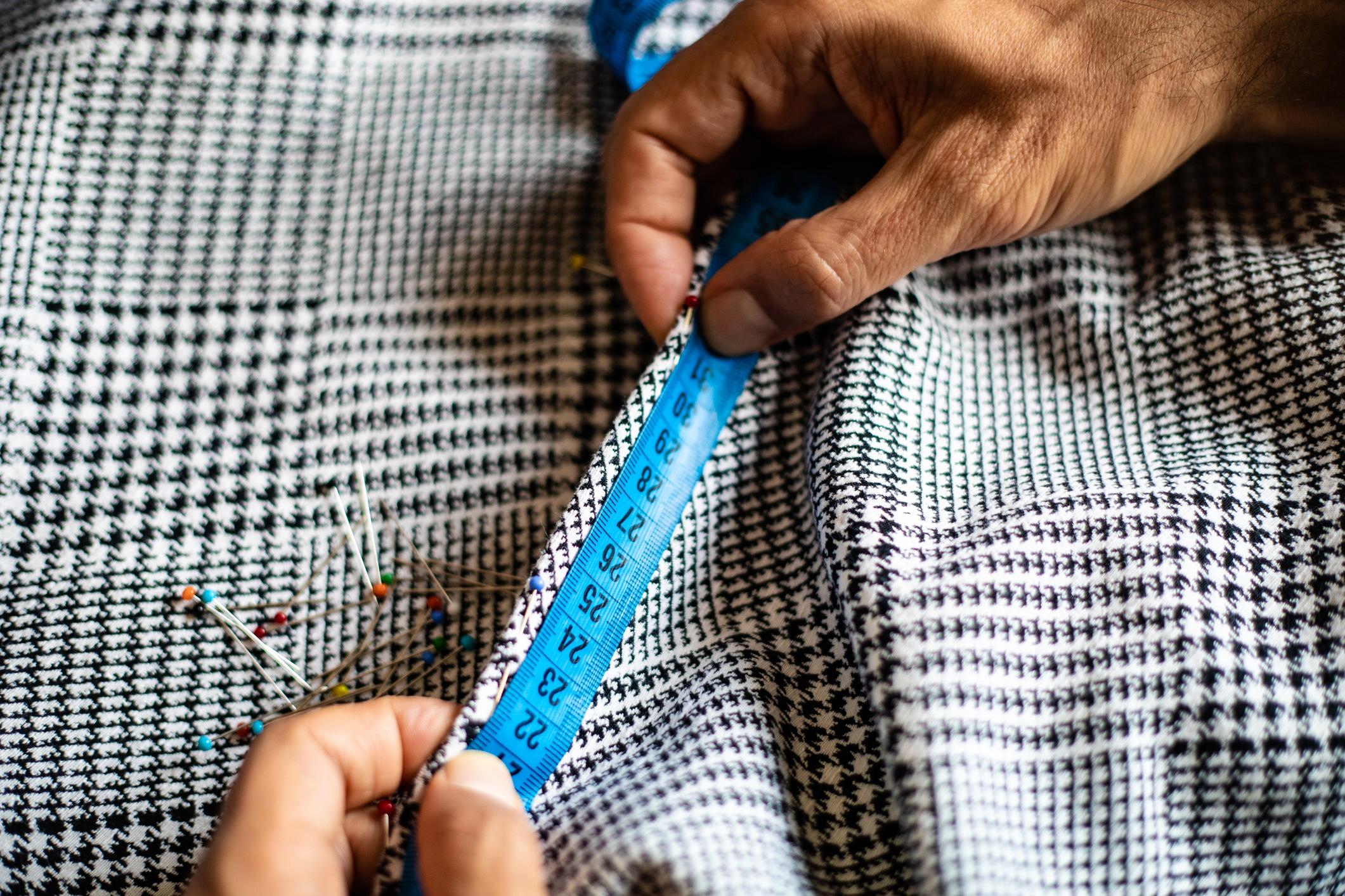 Ompelija mittaa mittanauhalla kangasta.