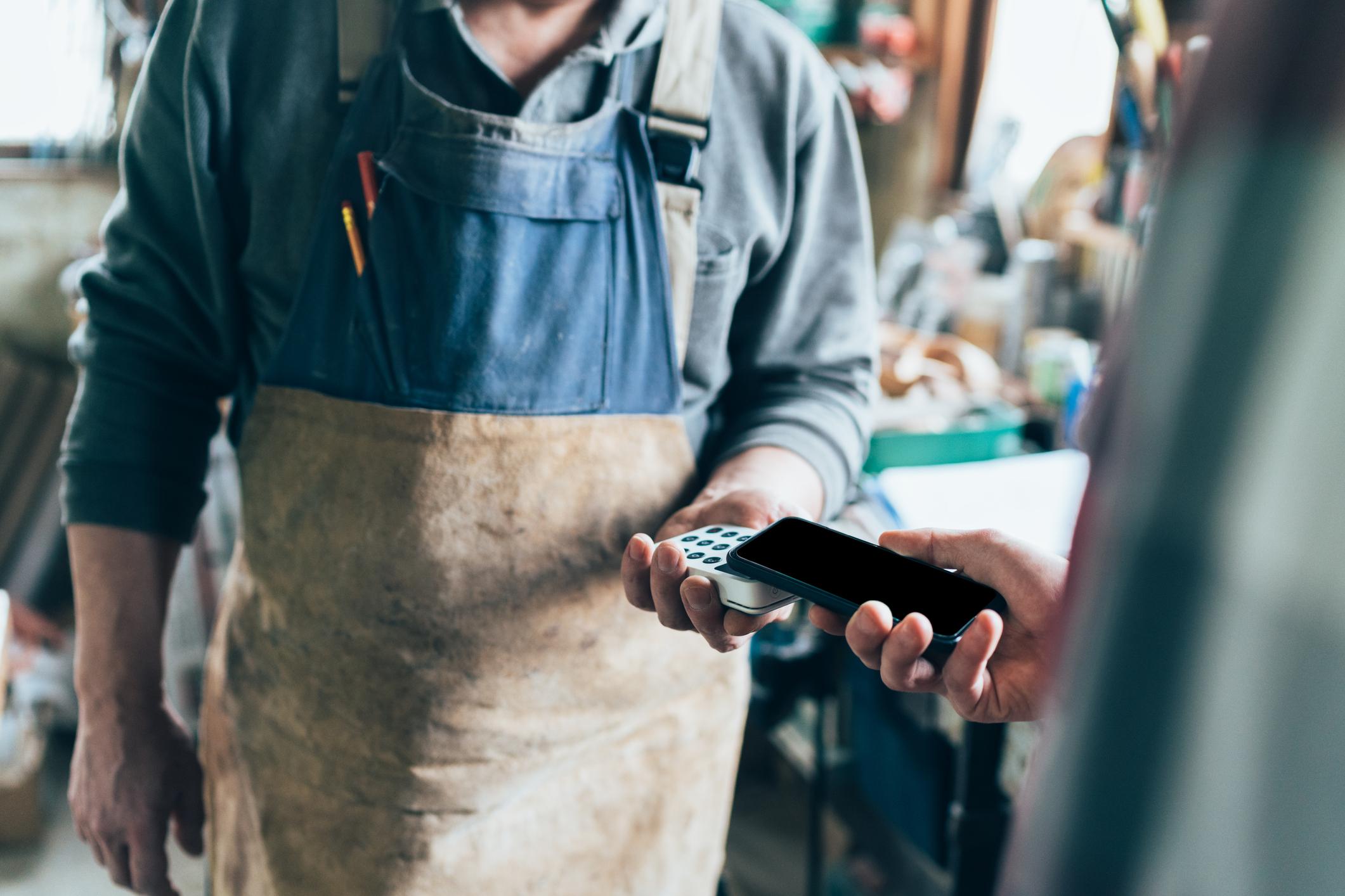 Käsityöläinen veloittaa asiakasta, joka maksaa puhelimellaan.