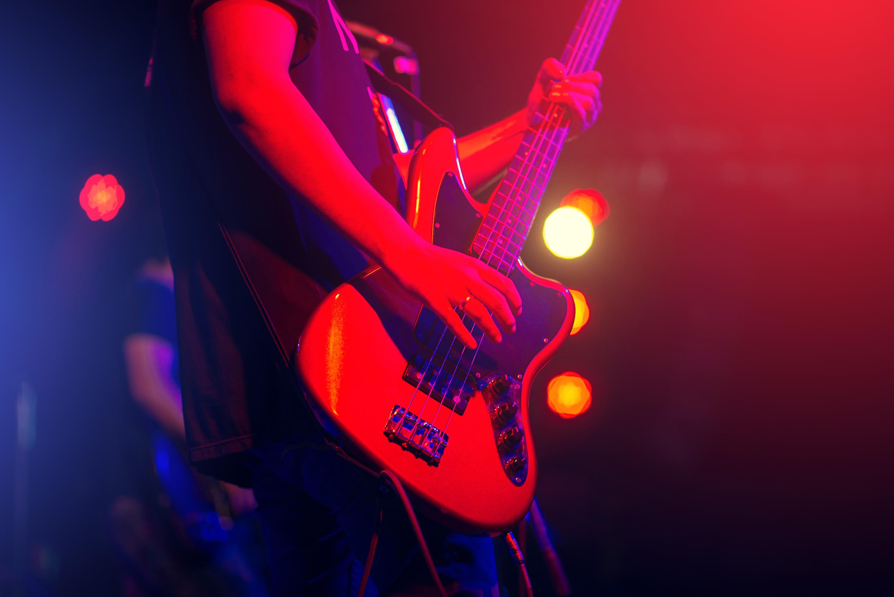 Kitaristi soittaa sähkökitaraa lavalla.