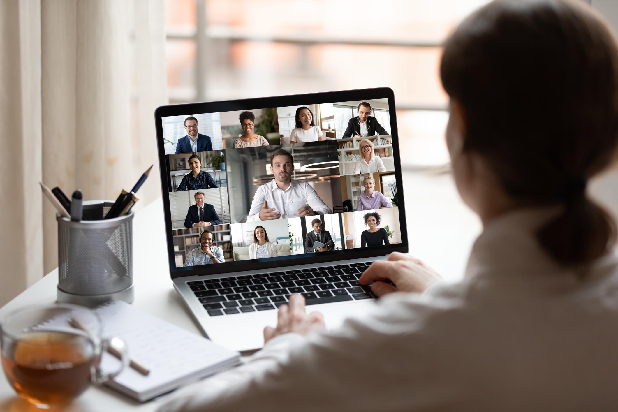 Nainen osallistuu etäkokoukseen kannettavalla tietokoneella.