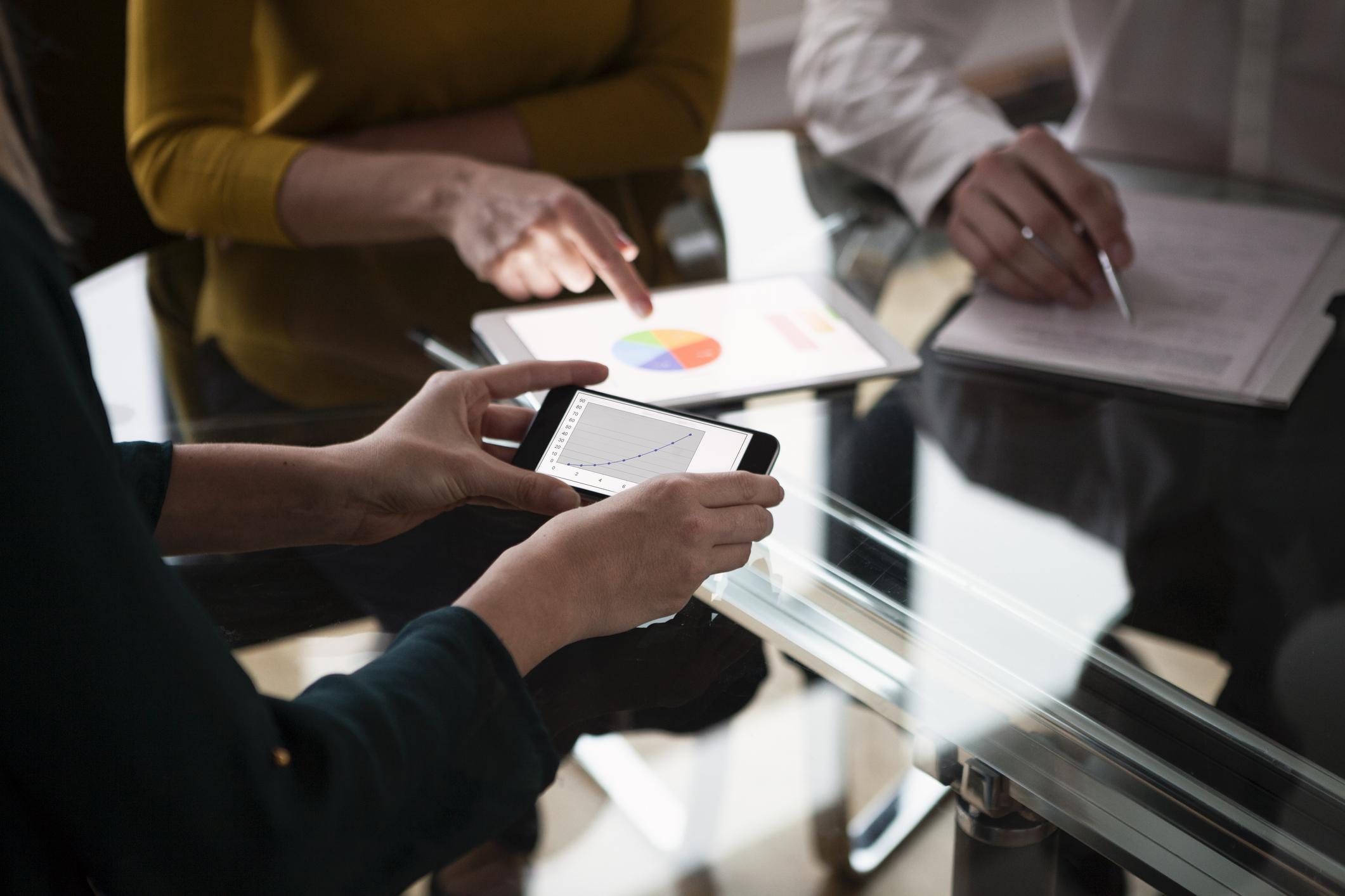 Ihmiset tekevät suunnitelmaa pöydän ääressä älypuhelimen, tabletin ja muistivihon avulla.