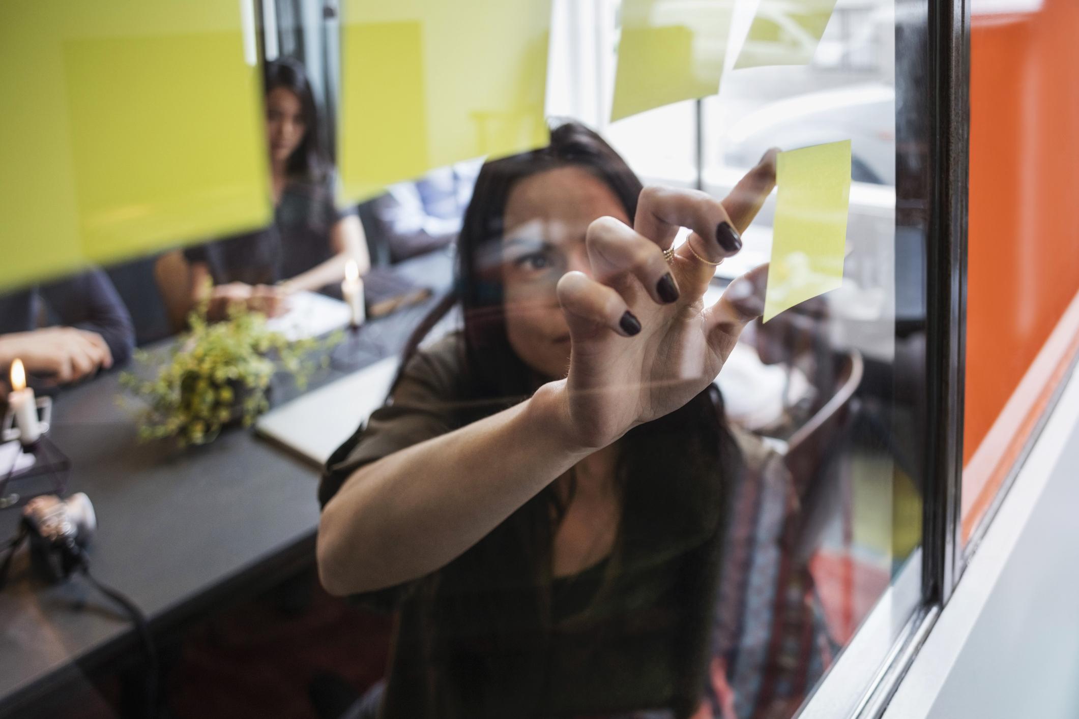 Nainen kiinnittää muistilappua lasiseinään palaverissa.