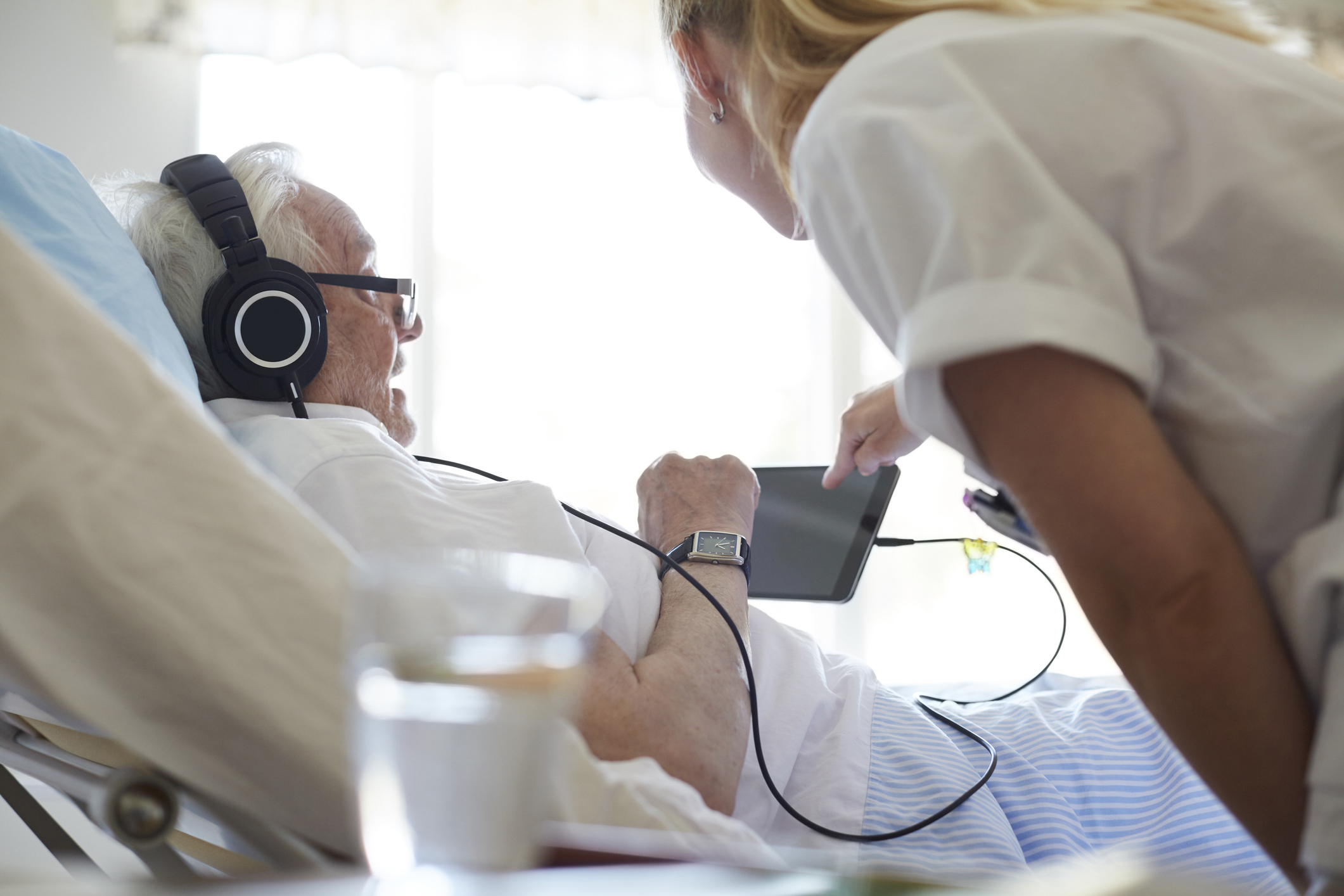 Hoitaja auttaa sängyssä makaavaa vanhusta käyttämään tablettia ja kuulokkeita.