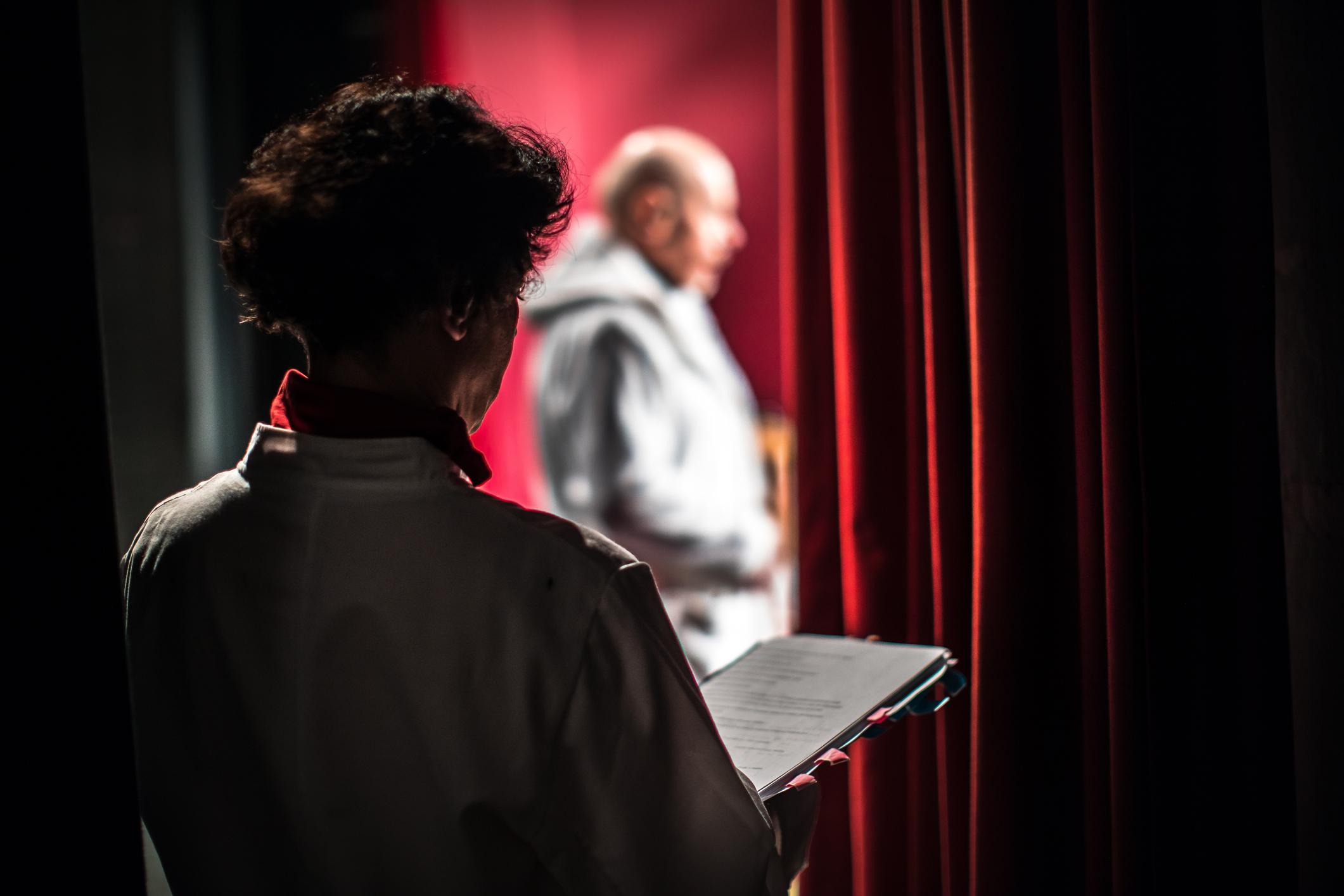Näyttelijä seuraa vuorosanoja lavan takana, kun toinen näyttelijä on näyttämöllä.